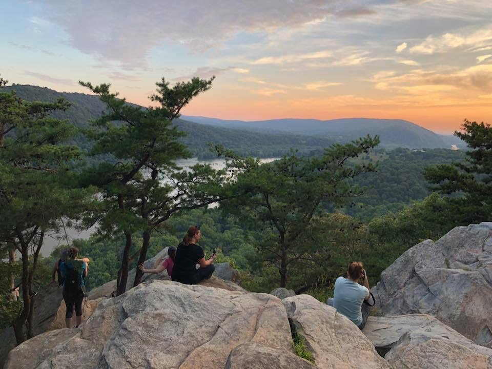 hikers sitting on Weverton Cliffs boulders at sunset